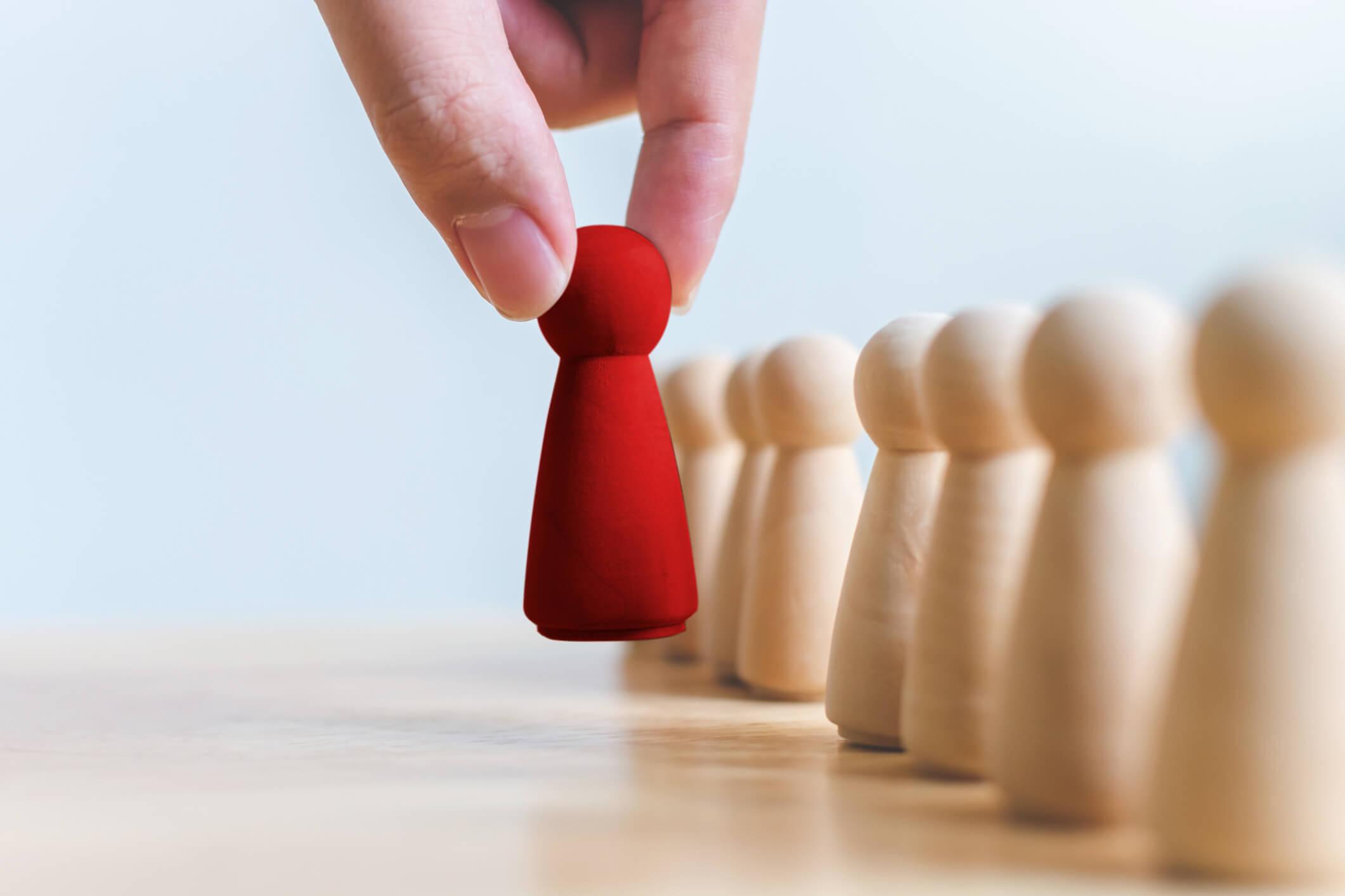 Farbige Schachfigur wird von einer Hand genommen