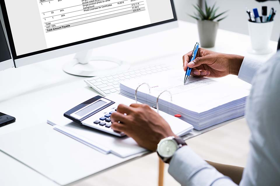 Person-schreibt-Rechnungsvorlage-am-Computer