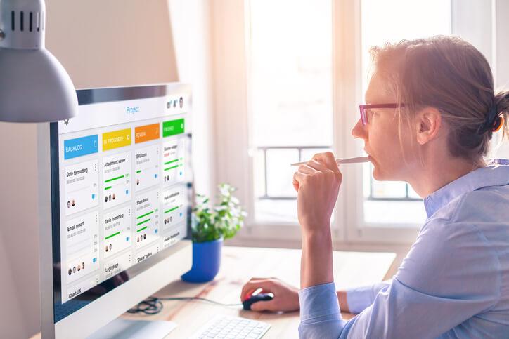 Frau mit Brille sitzt vor einem Computer Bildschirm