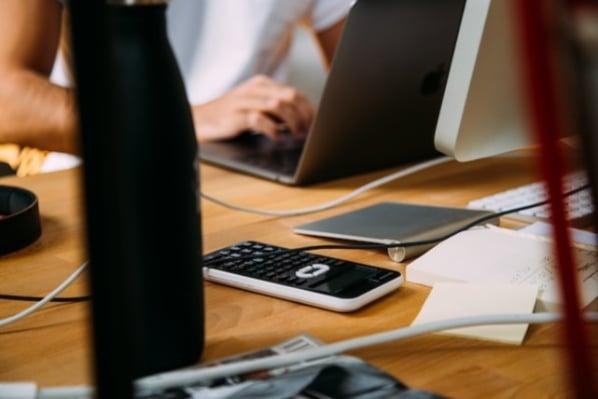 Taschenrechner und Kugelschreiber liegen vor farbigem Hintergrund