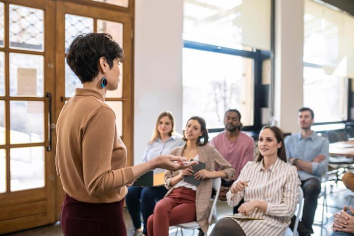 Frau hält Vortrag vor kleiner Gruppe