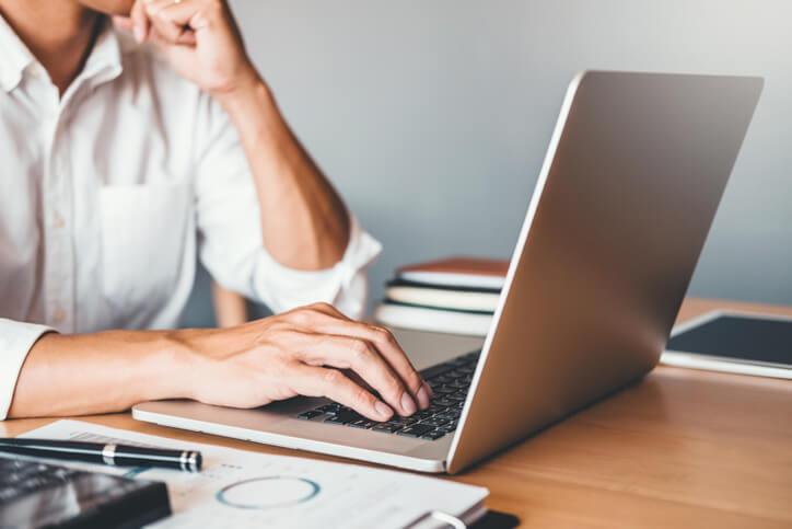 Mann sitze am Laptop und stützt seinen Kopf auf eine Hand
