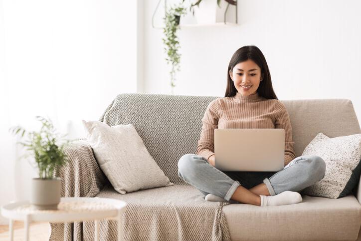 Frau arbeitet auf der Couch mit Laptop