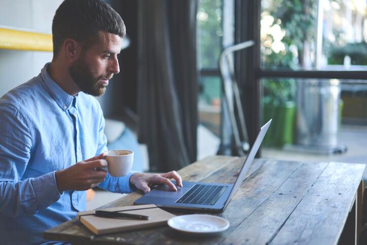 Mann hält Kaffeetasse in einer Hand und arbeitet an einem Laptop