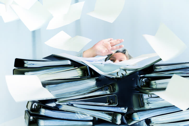 Mann verschwindet hinter hohem Dokumentenstapel