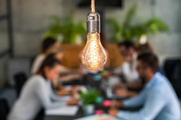 Glühbirne leuchtet im Vordergrund vor Team-Meeting