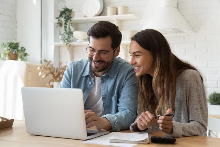 Mann und Frau sitzen gemeinsam am Tisch mit Laptop