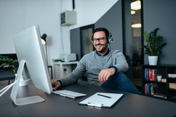 Mann mit Headset sitzt am Schreibtisch und lacht