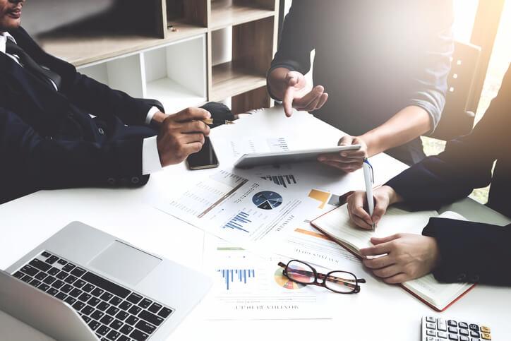 Team-sitzt-an-einem-Tisch-und-arbeitet-an-Produktlebenszyklusanalyse