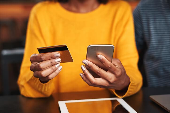 Frau hält Kreditkarte und Smartphone in den Händen