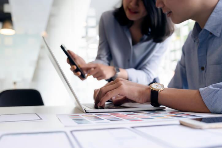 Kollegin-und-Kollege-testen-User-Experience-Usability-und-UX-Design-mit-Smartphone-und-Laptop