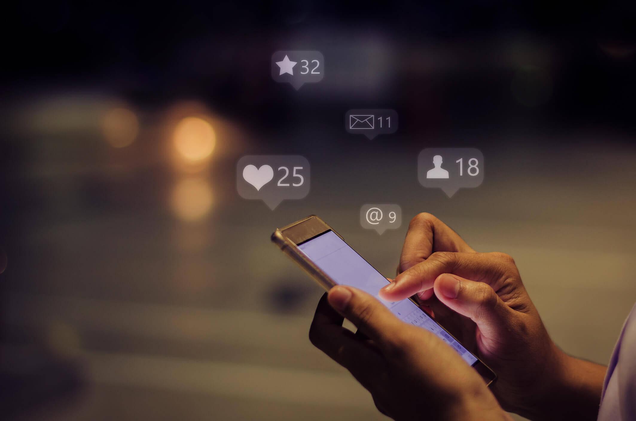 Hand hält erleuchtetes Smartphone in den Händen