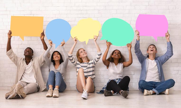 Menschen halten Sprechblasen in verschiedenen Farben hoch