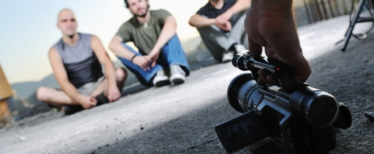 three young man siting on ground while modern video camera recording-213803-edited