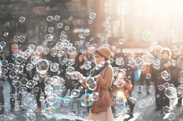 Eine Frau bläst Seifenblasen um Crowdfunding Plattformen zu symbolisieren